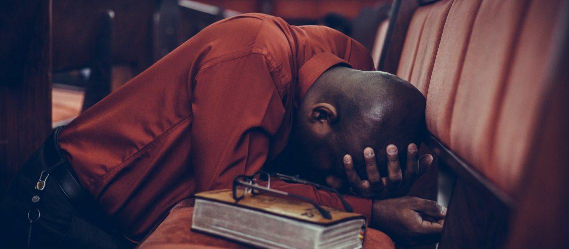 Photo of a man praying in church